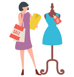Woman looking at dress on mannequin in shop vector