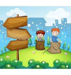 Two boys playing sack race near the arrow boards vector image
