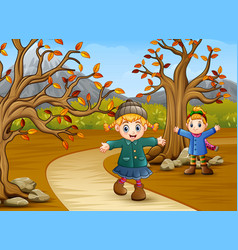 Happy kids playing in the autumn park vector