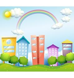 A rainbow above tall buildings vector