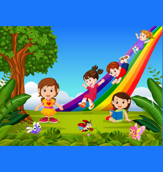 Cartoon kids sliding down the rainbow vector