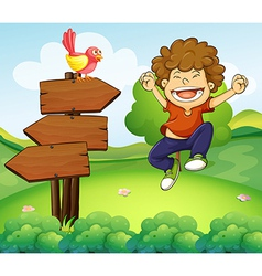 A happy young boy beside the three wooden arrows vector image vector image