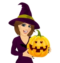 Young woman dressed like witch holding pumpkin vector