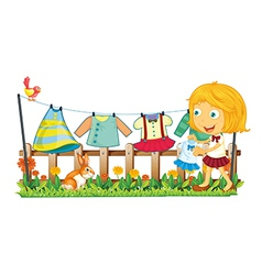 A girl hanging her clothes at the garden vector image