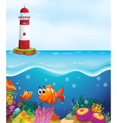 A light house fishes and coral in sea vector