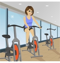 Young woman doing indoor biking exercise at gym vector