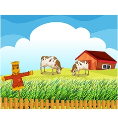 A scarecrow with two cows inside the fence vector image