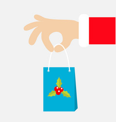 santa claus hand holding gift shopping paper bag vector image