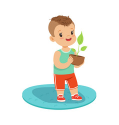 Cute little boy standing and holding a plant in a vector