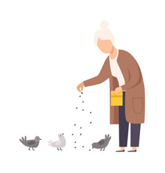 Senior woman standing and feeding pigeons vector
