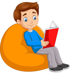 young boy reading a book sitting on big pillow vector image