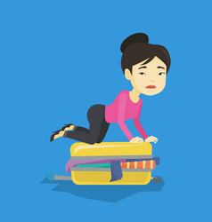 Young woman trying to close suitcase vector