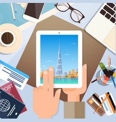 Hand hold tablet computer with dubai skyline vector