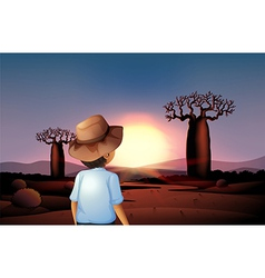 A boy with a hat watching the sunset in the desert vector image