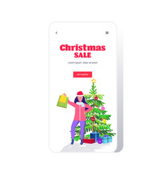 girl in santa hat holding shopping bags standing vector image
