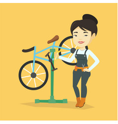 Asian bicycle mechanic working in repair shop vector