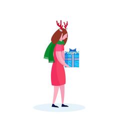 Woman wearing deer horns holding gift box happy vector