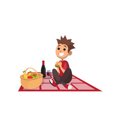 young happy boy sitting on picnic plaid and eating vector image