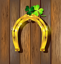 Gold horseshoe with Shamrock on wooden vector image