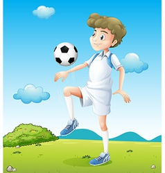 A boy playing soccer during daytime vector
