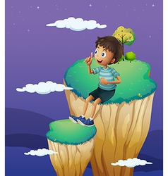 A boy sitting above the high rock formation vector image