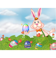 A bunny with eggs at the garden vector image