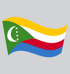 Flag of comoros waving on gray background vector