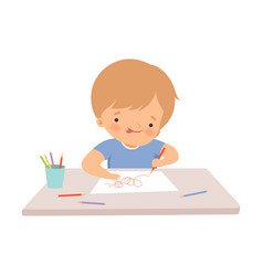 boy sitting at desk and drawing picture vector image