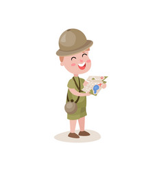 Excited little boy scout holding map in hands vector