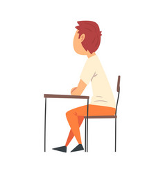 Cute boy student sitting at desk in classroom vector