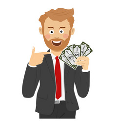 Happy business man pointing to fan of dollar bills vector