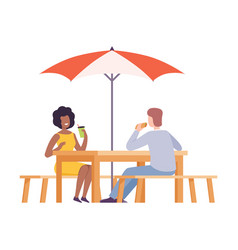 young man and woman sitting at table drinking vector image