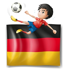 A boy playing soccer in front of the flag of vector image vector image