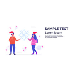 couple in santa hats holding snowflake merry vector image