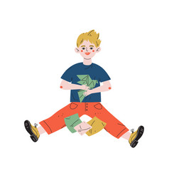 boy sitting on floor and making origami hobby vector image