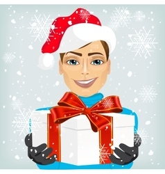 Young man wearing a santa hat offering gift vector image