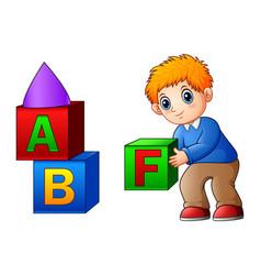 Cartoon boy playing with alphabet cubes vector