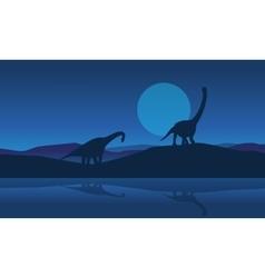 Silhouette of brachiosaurus on riverbank scenery vector image vector image