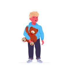 little boy holding teddy bear cute child standing vector image