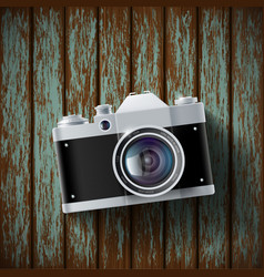 old film camera lying on a wooden surface vector image