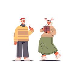 senior couple in santa claus hats having fun with vector image