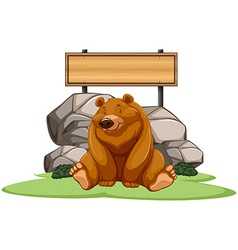 Grizzly bear sitting next to the sign vector