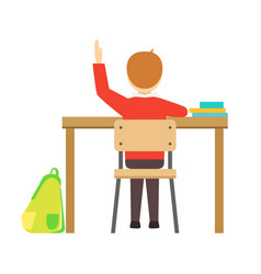 boy raising hand sitting at his desk in classroom vector image vector image
