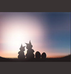 silhouette of easter bunnies against a sunset sky vector image