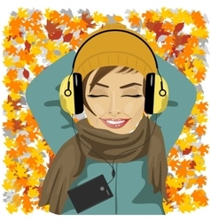 woman listening to music lying on autumn leaves vector image vector image
