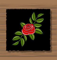 Embroidery rose on a dark flap cloth and wooden vector