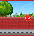 brick wall with stop sign on the pavement vector image