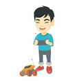 asian boy playing with a radio-controlled car vector image
