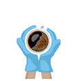 hands in christmas mittens hold a cup of coffee vector image