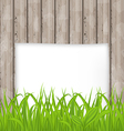Green grass and paper sheet on wooden texture vector image